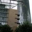 Kippendes Eckgebäude gegen Glassäule 1